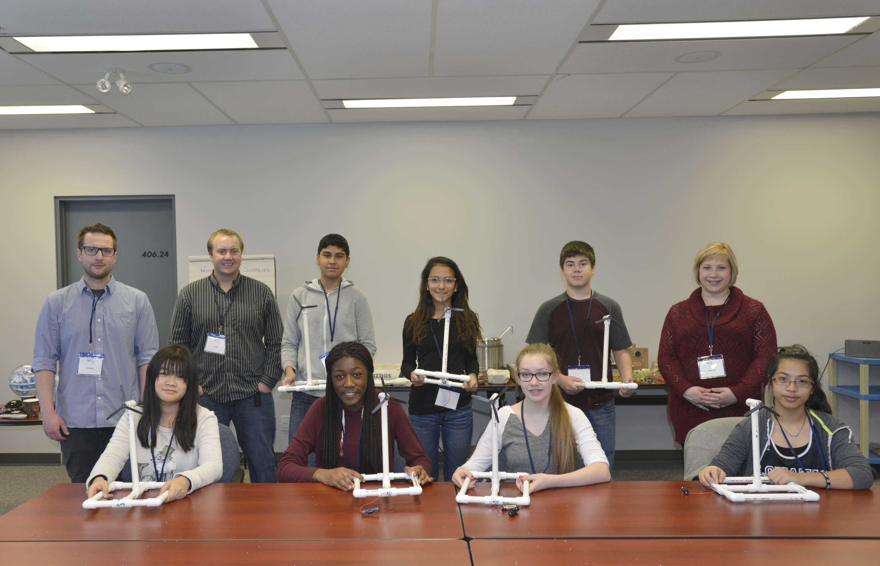 7 grade 9 students stand with their completed wind turbine models