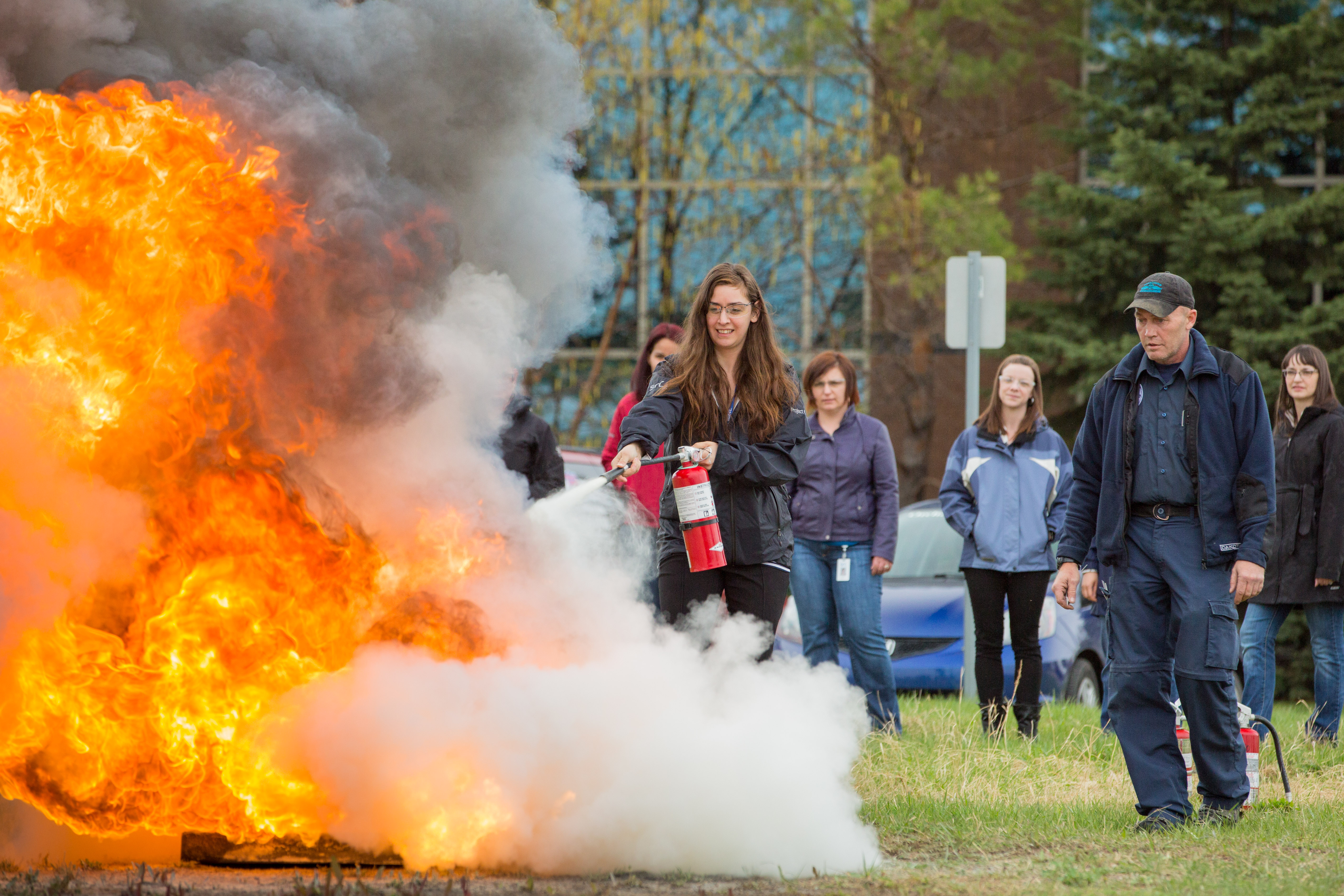 Woman extinguishes fire during fire extinguisher training