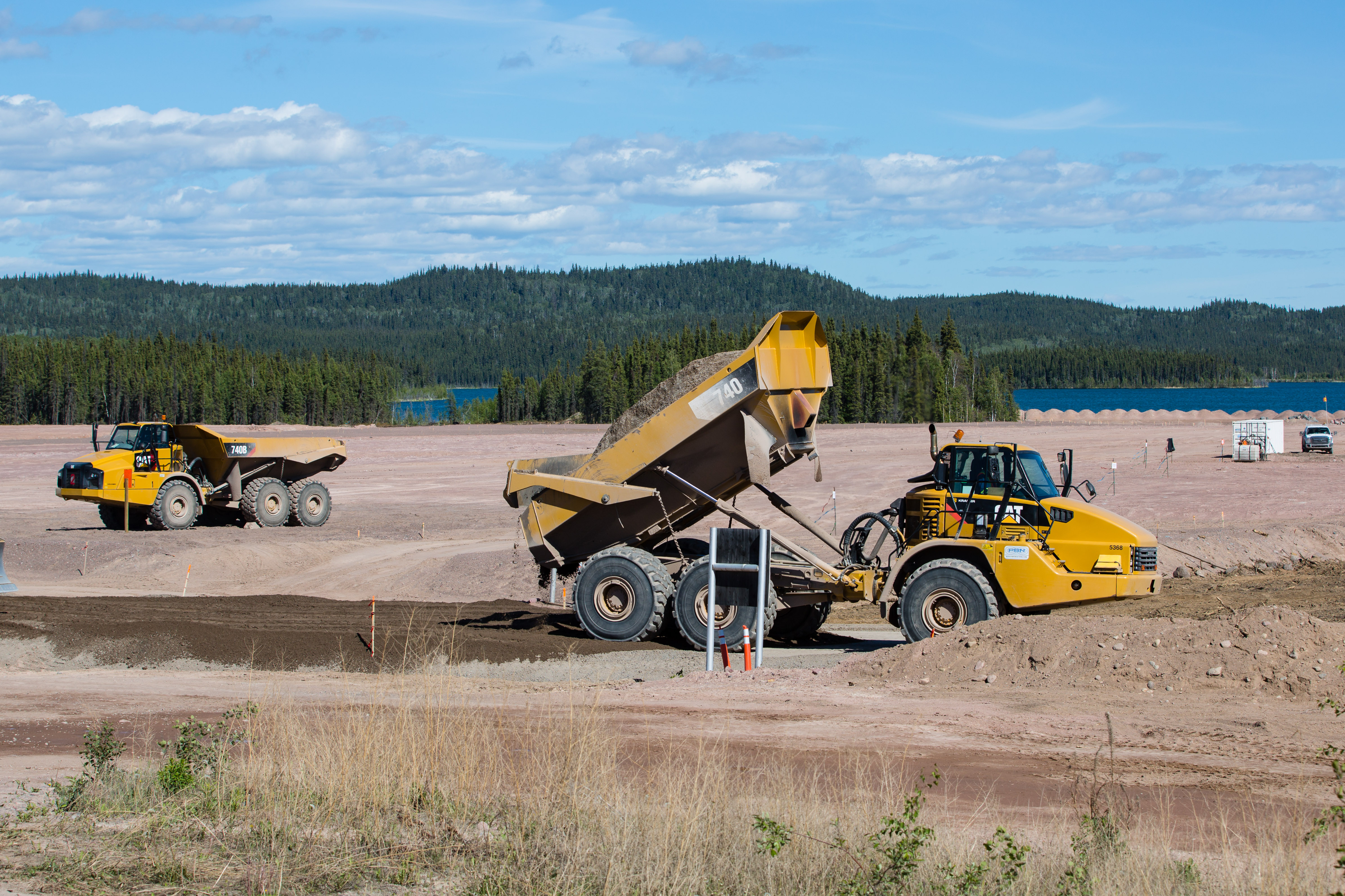 Large trucks haul material to cover Lorado site.