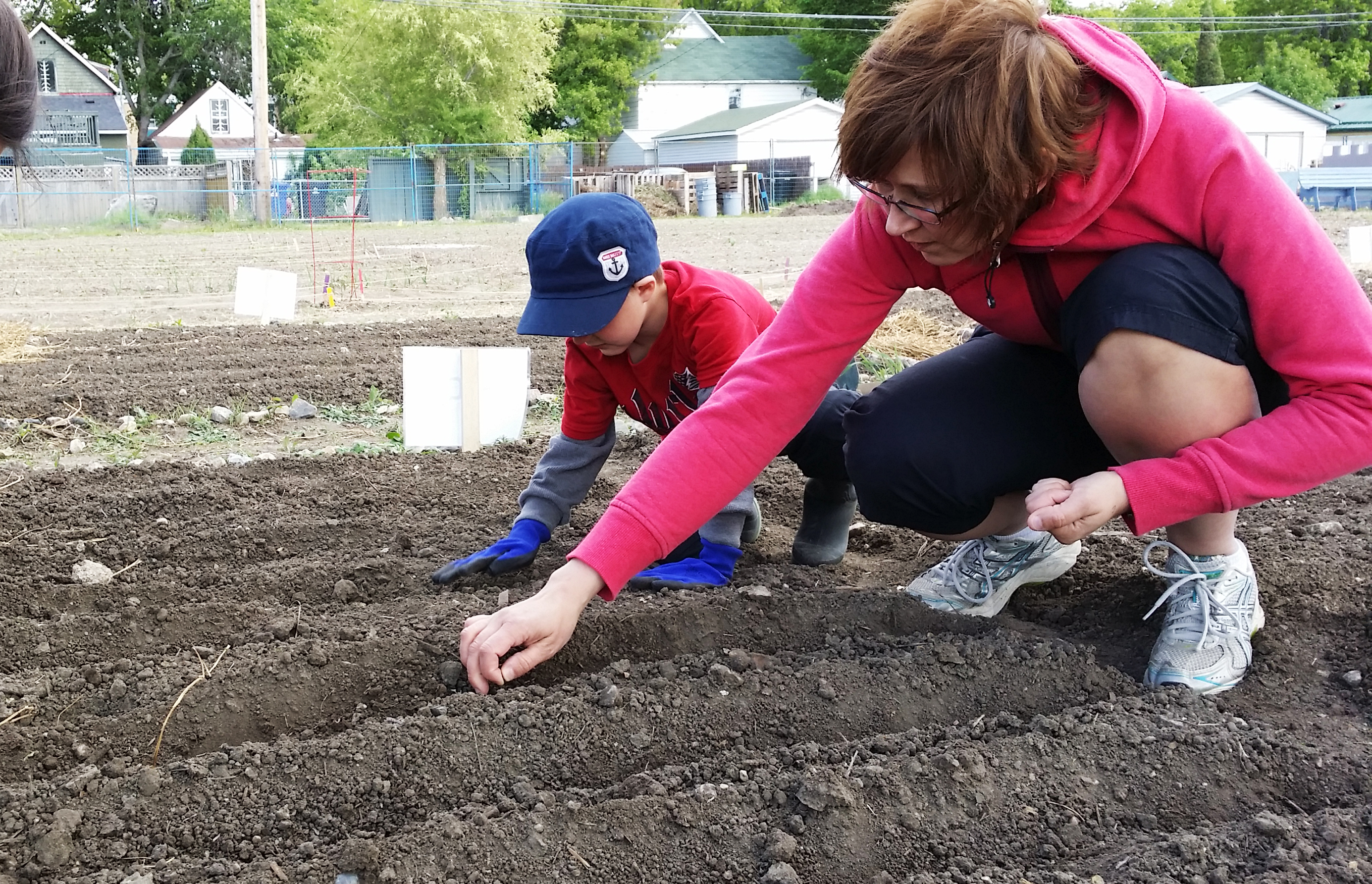 a woman and young boy plant seeds