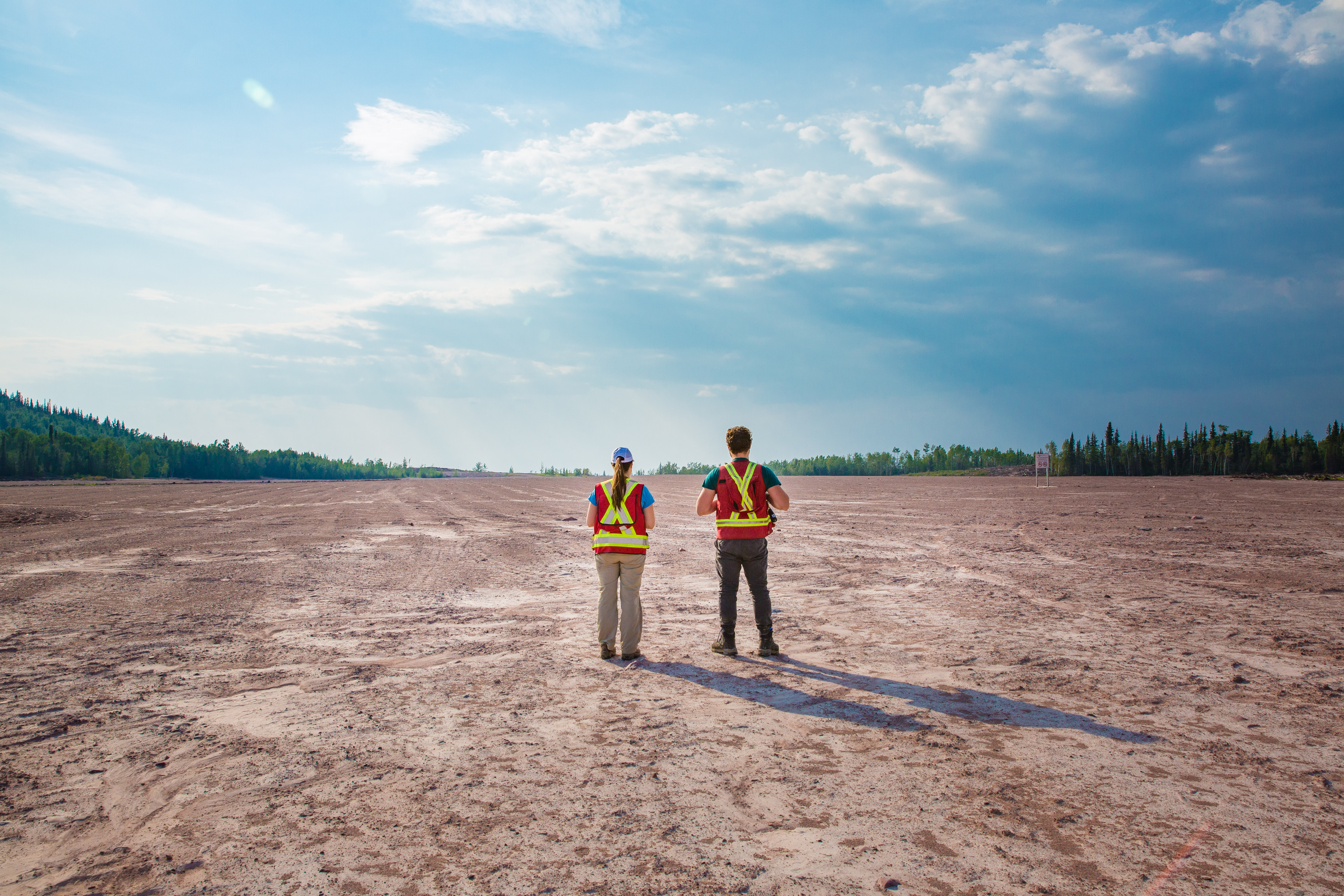 two field workers walk over reclaimed mill site