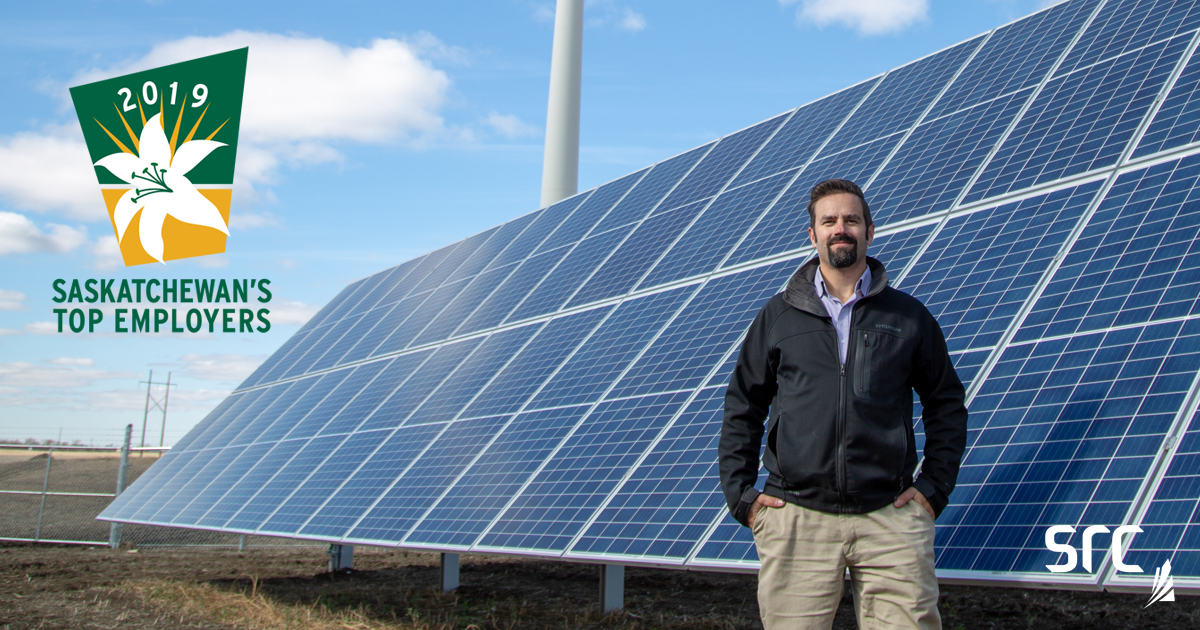 src employee stands in front of solar panel with sask top employer logo