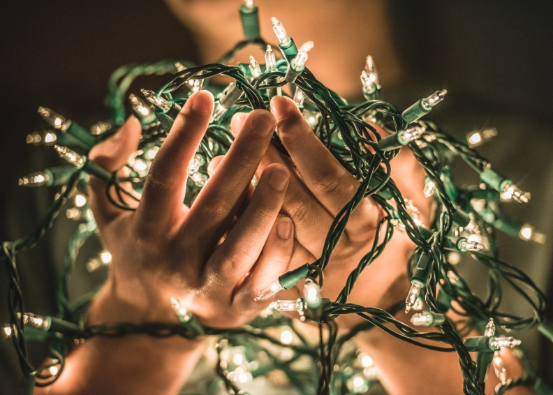 src hands holding christmas lights
