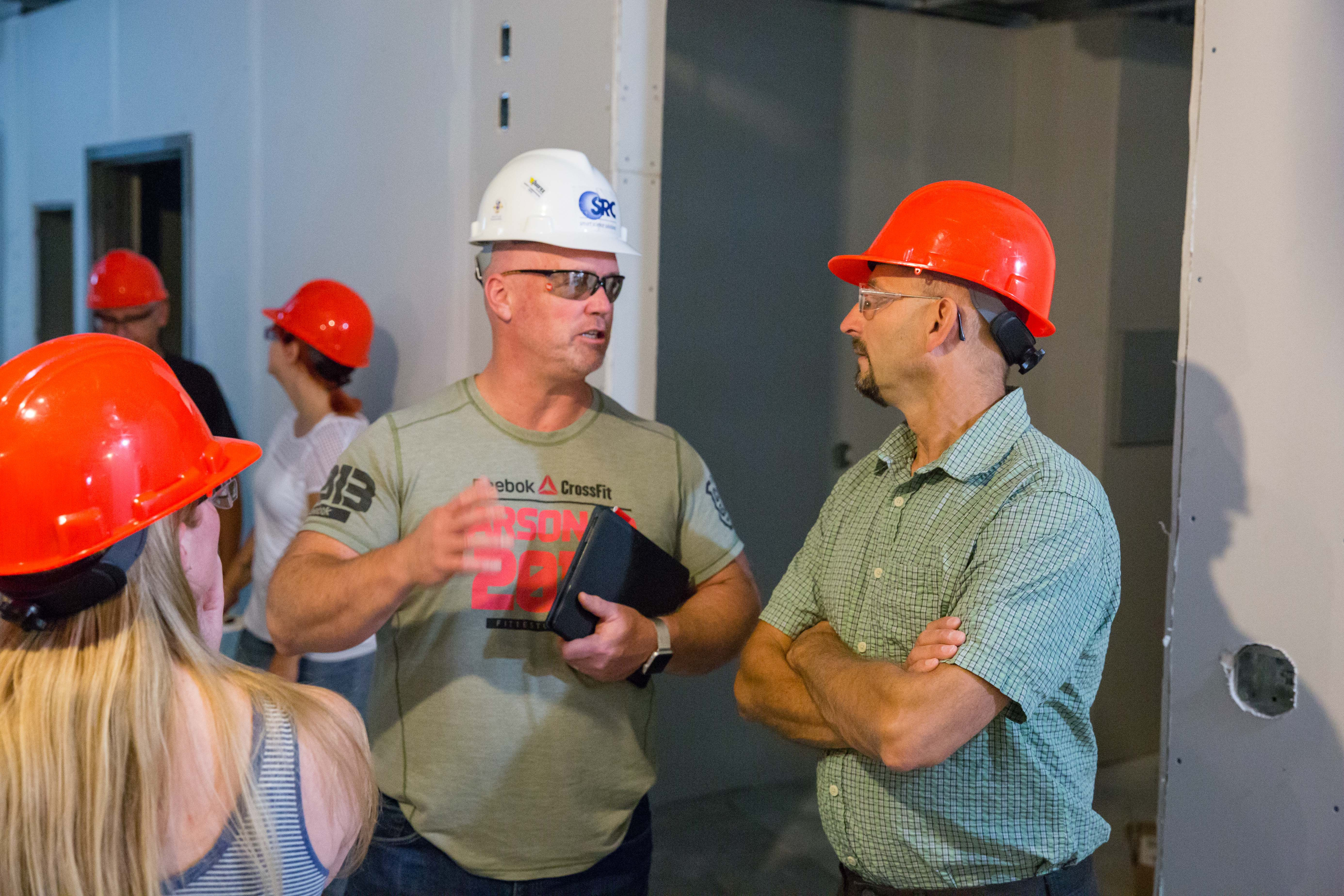 two men in hard hats talking