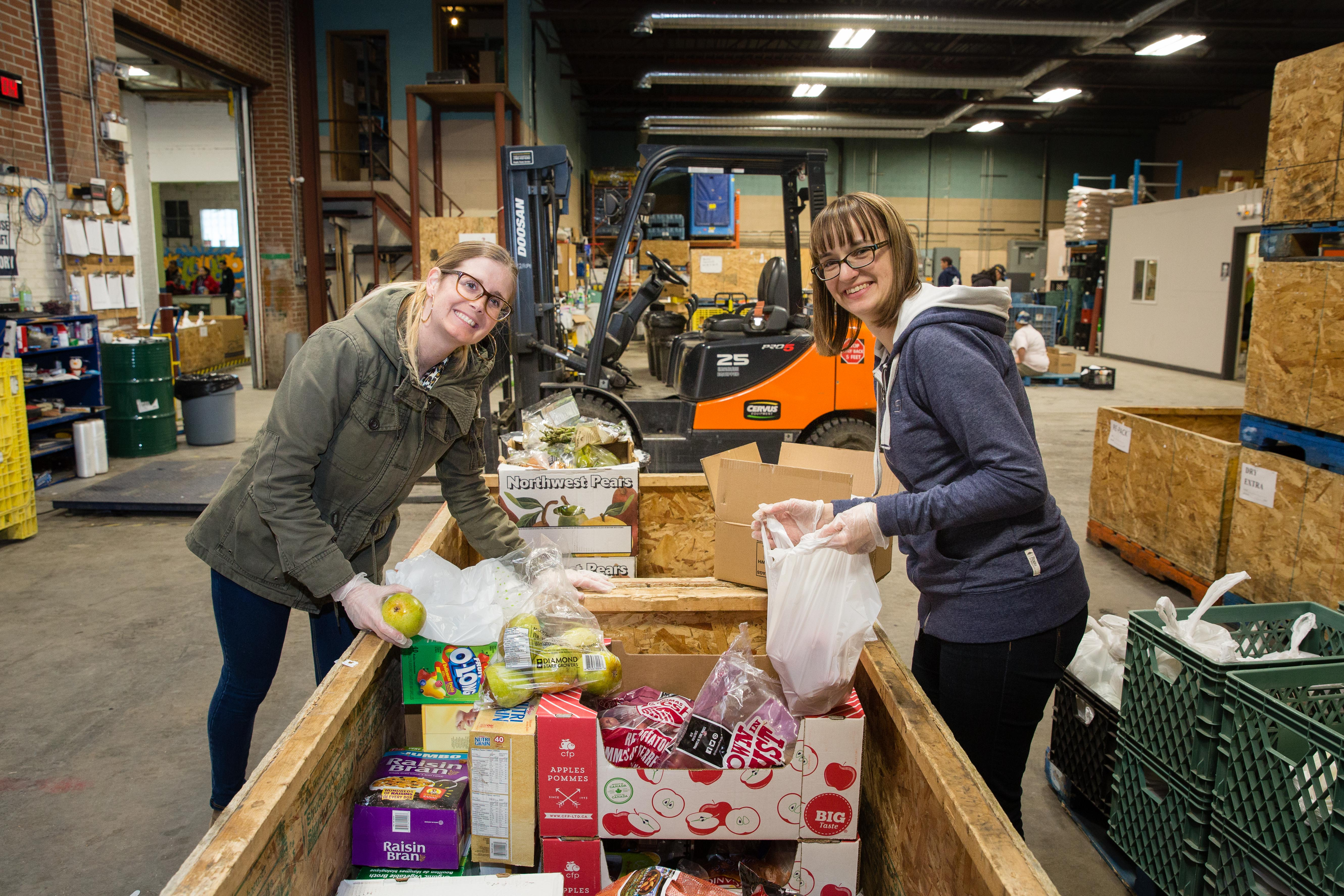 two src employees sort bins of cans at food bank