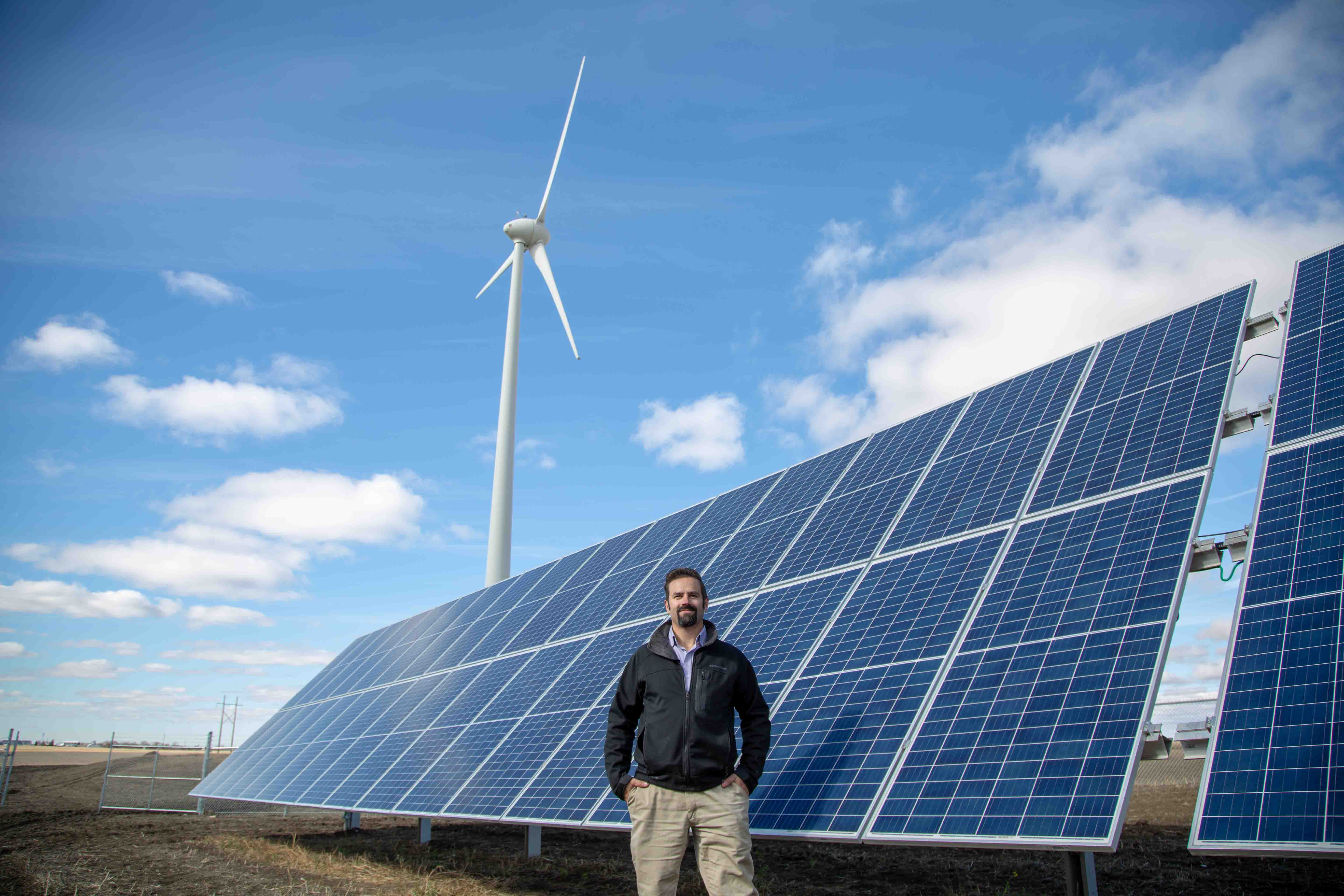 src research engineer stands in front of hybrid solar panel and wind power system
