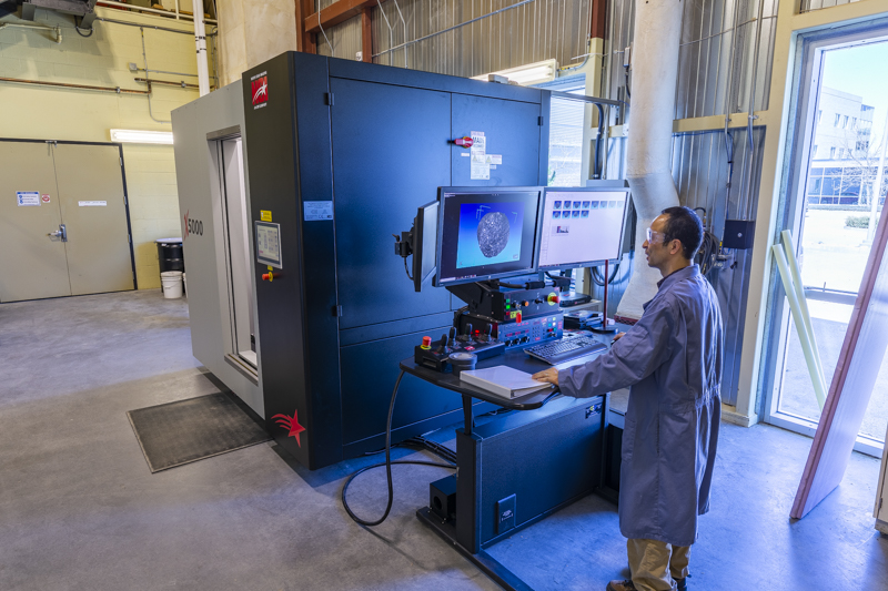 src research engineer operates industrial ct scanner in oil and gas lab