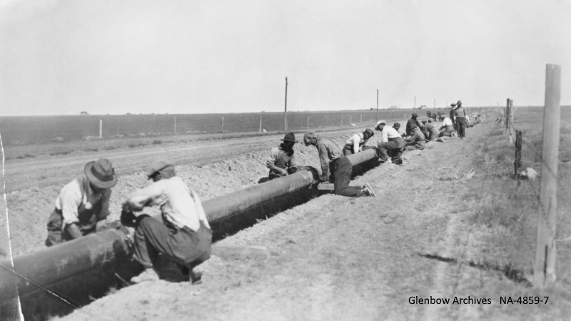 Laying pipe for pipeline between Turner Valley and Calgary, southern Alberta.