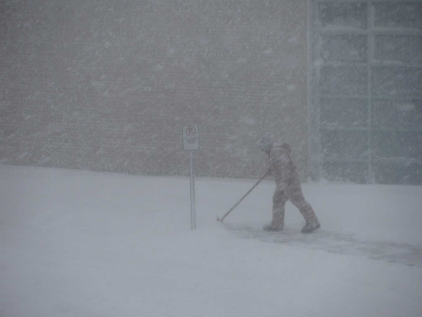 man shovelling in snowstorm