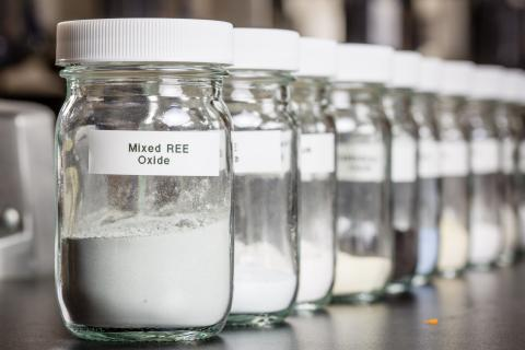 Row of glass jars filled with rare earths