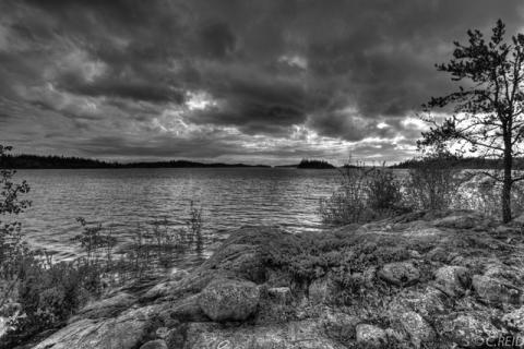 View of lake from rugged shore with dramatic clouds