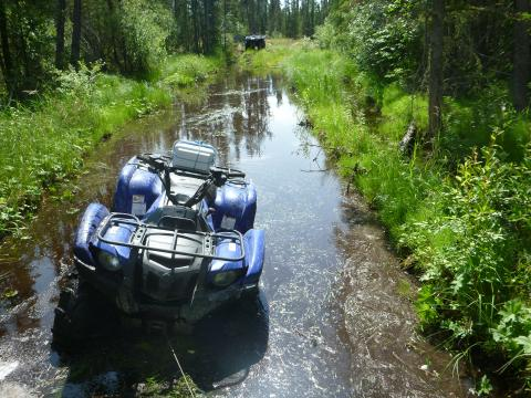 Quad stuck in mud in northern forest