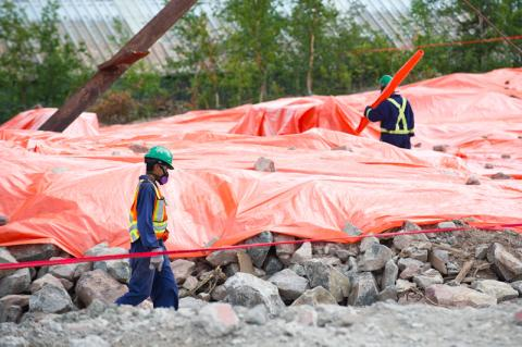 Two workers in personal protective equipment at a demolition site.