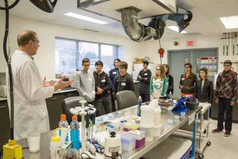 Students in a lab listening to instructor