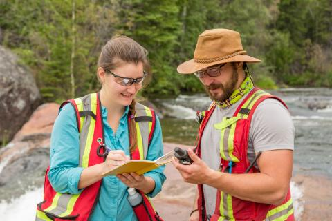 two field workers look at water sample