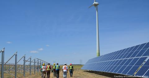 field workers walking towards src cowessess wind turbine with solar panels