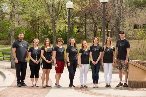 SRC employees stand outside wearing 70th t-shirts