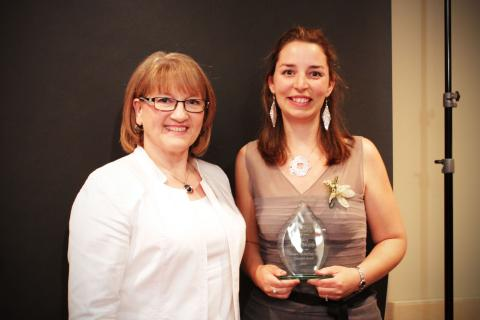 two women, one holding an award