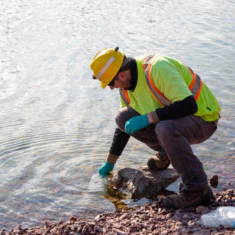 src remediation specialist dips container in water to sample