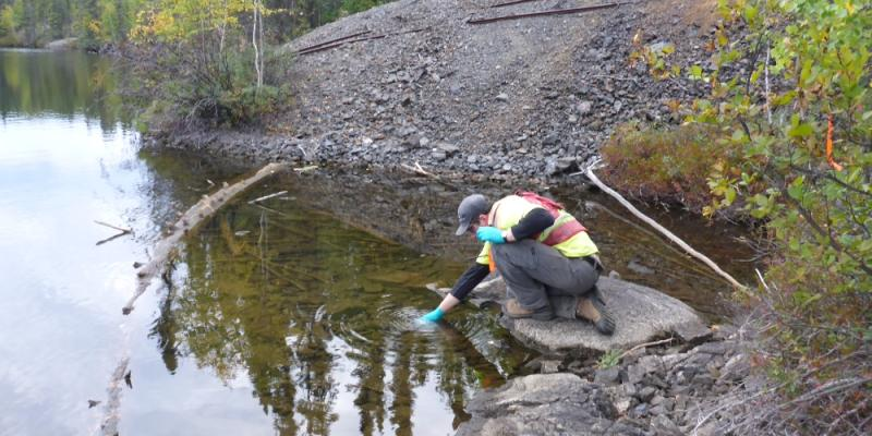 src remediation specialist collects water sample at lake