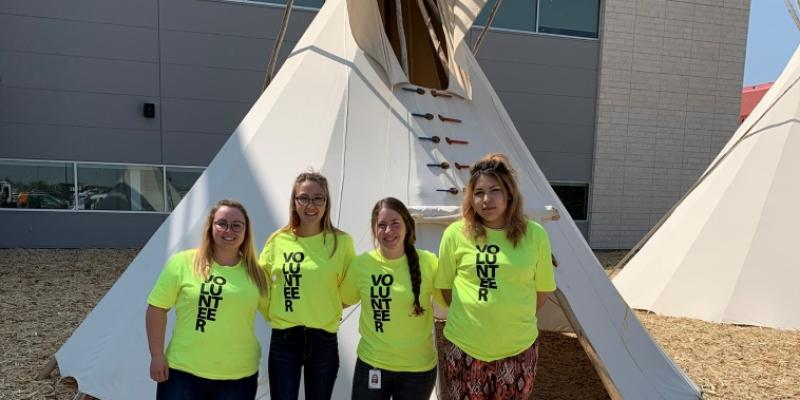 four female src students stand in front of a tipi
