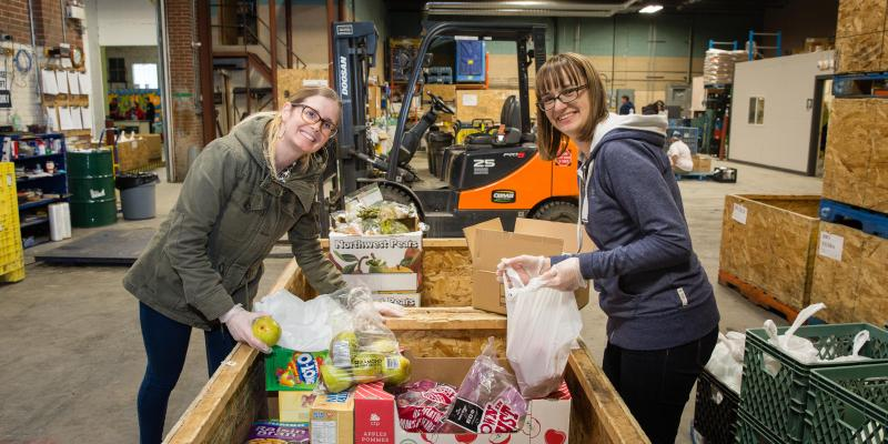 two smiling volunteers at food bank