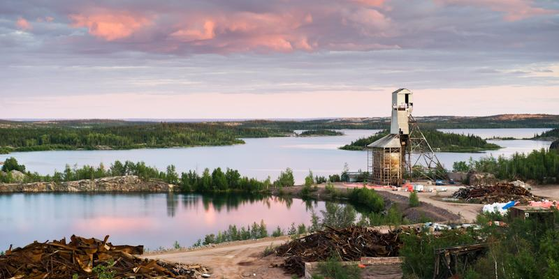 debris piles and headframe in remote lake area against sunset