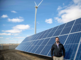 src employee stands in front of cowessess solar panels and wind turbine